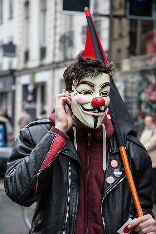 Un homme portant un masque des Anonymous dans le cortège du Front de Gauche, le 18 mars 2012 à Paris.