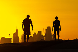 London, October 27 2017. Two runners are seen in silhouette as the day breaks over London's skyline, seen from Primrose Hill. © Paul Davey