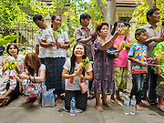 "12 JULY 2014 - PHRA PHUTTHABAT, SARABURI, THAILAND: People wait to present flowers to the monks before the Tak Bat Dok Mai at Wat Phra Phutthabat in Saraburi province of Thailand. Wat Phra Phutthabat is famous for the way it marks the beginning of Vassa, the three-month annual retreat observed by Theravada monks and nuns. The temple is highly revered in Thailand because it houses a footstep of the Buddha. On the first day of Vassa (or Buddhist Lent) people come to the temple to ""make merit"" and present the monks there with dancing lady ginger flowers, which only bloom in the weeks leading up Vassa. They also present monks with candles and wash their feet. During Vassa, monks and nuns remain inside monasteries and temple grounds, devoting their time to intensive meditation and study. Laypeople support the monks by bringing food, candles and other offerings to temples. Laypeople also often observe Vassa by giving up something, such as smoking or eating meat. For this reason, westerners sometimes call Vassa ""Buddhist Lent.""    PHOTO BY JACK KURTZ"
