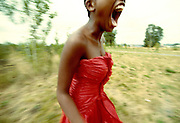 Woman running in field screaming with red dress