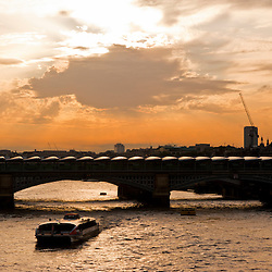 A boat on the River Thames passes below Blackfriars Bridge in London. The bridge has installed 4,400 solar panels on the roof creating the biggest solar bridge in the world.