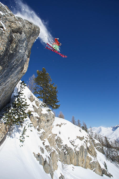 Male Skier jumping off cliff on steep mountainside, Skiing Serre Chevalier