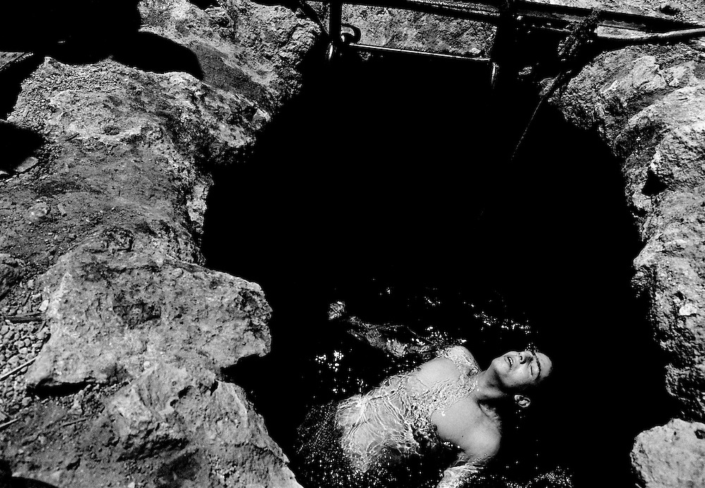 Mario bathes in an old Palestinian well outside the settlement of Kiriyat Arba.  Hebron 2001.