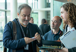 Director, Douglas Mackinnon and Composer David Arnold attend a the first ever screening of Good Omens in its entirety at the Edinburgh International Film Festival<br /> <br /> Pictured: David Arnold signing autographs with Good Omens fans