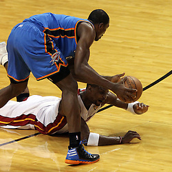 Jun 21, 2012; Miami, FL, USA; Oklahoma City Thunder power forward Serge Ibaka (9) and Miami Heat power forward Chris Bosh (1) go for a loose ball during the first quarter in game five in the 2012 NBA Finals at the American Airlines Arena. Mandatory Credit: Derick E. Hingle-US PRESSWIRE