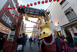 © licensed to London News Pictures. London, UK 22/01/12. A dragon mascot entertains visitors as people fill Chinatown in London for shopping and sharing the excitement of Chinese New Year on the day before Chinese New Year's Eve. Photo credit: Tolga Akmen/LNP