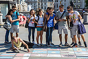 Tourists place money on their country flag, a project by a homeless group to raise money.  Trafalgar Square, London.