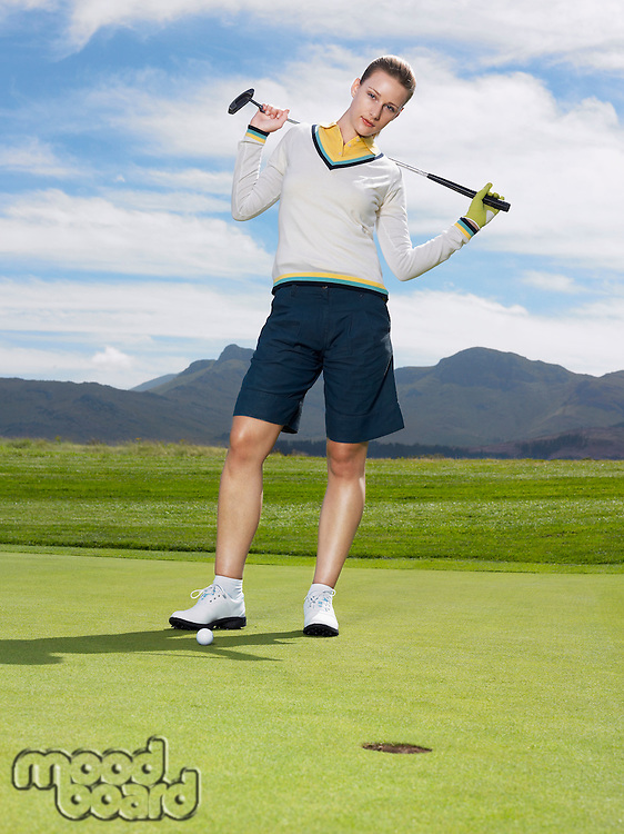 Young golfer standing on green portrait