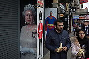 A foreign family walk past the images of Queen Elizabeth II, a guardsman and Superman, on 3rd February 2017, in London, England.