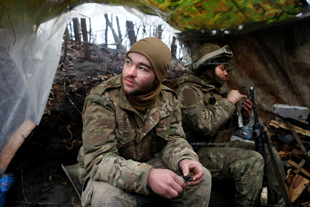 Cowboy (le.) sits beside Charlie who cleans his Kalashnikov in the frontline trench.<br />