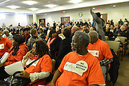 """Feb. 25, 2013 - Mineola, New York, U.S. - Front row, L to R in orange shirts, CHAVON DARRELL, EUNICE REDD, JOE LOUIS BROWN, all of Hempstead, are members of the New York Community for Change organization attending Nassau County Legislature meeting to show they are against the controversial Redistricting Map proposed by Republicans. When a short recess was announced, LINDA JOHN, of Hempstead, standing ar right, asked audience, """"How many of you are against the redistricting plan?"""" and many clapped their hands. The legislature postponed the vote on the map shortly before 1 AM the morning of February 26, nearly 12 hours after the meeting started on 1:30 PM Feb. 25."""