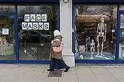 As the Coronovirus pandemic takes hold across the UK, with 53 cases now reported by health authorities, an Muslim lady walks past the window of a medical equipment business in south London, displays a face masks sign and surgical masks on a skeleton mannequin, on 4th March 2020, in London, England.