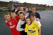 Group of boys wearing football strips, posing for a group hug on a concrete football pitch, UK, 2000's