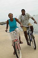 Couple cycling on beach smiling