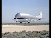 The jumbo JUMBO jet: Nasa's super-sized plane can carry 26 tonnes of spaceship parts and still travel at 290mph<br /> <br /> It might look like a giant whale in the sky, but this super-size plane is in fact Nasa's answer to shipping spacecraft components around the world.<br /> Dubbed the Super Guppy, the aircraft is able to swallow other planes whole and has played a vital role in missions including Gemini and Skylab.<br /> The Aero Spacelines Super Guppy was first created in 1962 as a successor to the aptly-named Pregnant Guppy cargo aircraft.<br /> <br /> <br /> Pregnant Guppy helped achieve President Kennedy's goal of getting to the moon by the end of the 1960s.<br /> Without Pregnant Guppy, the only other way to get the Apollo rocket stages from California to Florida was on a slow boat through the Panama Canal.<br /> <br /> <br /> The Pregnant Guppy was so successful that ASI built a second larger Guppy for larger, heavier loads.<br /> There have been five Super Guppies built today, helping move spacecraft parts and fuel to vital locations,<br /> <br /> <br /> Nasa describes the craft, which looks like it shouldn't be able to fly, as 'an innovative composite rocket fuel tank.'<br /> Equipment and fuel is loaded and unloaded via a hinged nose at the front of the huge plane.<br /> The original Super Guppy measured 141 ft (43m) long by 25 ft wide (8m) and could carry 54,000lbs (24500kg) of cargo at a cruising speed of 300 mph.<br /> The later Super Guppy Turbine has a 156 ft (48m) wingspan, is143 ft (44m) long and 37 ft (11m) tall. It can carry a payload over 52,500 lbs (24,000kg)at 290 mph up to 564 miles.<br /> The most important difference between it and its predecessor was an upgrade to more reliable and readily available Allison T-56 turboprops.<br /> Airbus Industries commissioned and operated four SGT Super Guppy Transport aircraft to ferry large A300 fuselage sections throughout Europe during the last three decades of the 20th century.<br /> When Airbus retired its fleet to museums in 1997, Nasa was able to acquire the number four aircraft to replace its aging B377SG Supe