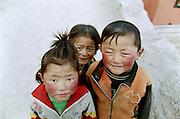 Three young tibetan children on the pilgrimage path of the monastery of Labrang, during the Great Prayer . They were following their parents who  walking along the circumambulation path (3km long) in the hope of improving their future life. The children were very fidgety and asked to be taken in picture, but suddenly stopped to move in front of the camera... Xiahe, province of Gansu, China, 03/01/2007.....<br /> <br /> [French] Trois enfants tib&eacute;tains sur le chemin de p&egrave;lerinage du monast&egrave;re bouddhique de Labrang, pendant Monlam Chenmo (La Grande Pri&egrave;re). Ils suivent leurs parents qui effectuent plusieurs fois par jour la circumambulation autour de monast&egrave;re (3km) dans l'espoir d'am&eacute;liorer leur vie future. Tr&egrave;s agit&eacute;s les enfants demand&egrave;rent &agrave; &ecirc;tre photographi&eacute;s mais se fig&egrave;rent soudain devant l'appareil. <br /> Xiahe, Province du Gansu, Chine, 1er Mars 2007.