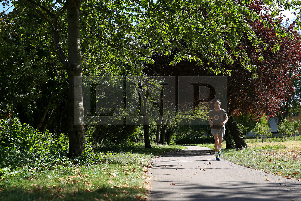 © Licensed to London News Pictures. 02/09/2019. London, UK. A jogger jogs on a sunny morning in a north London park with an autumnal coloured tree. Photo credit: Dinendra Haria/LNP