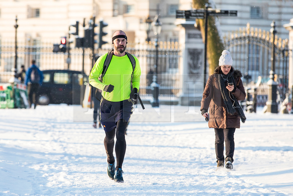 © Licensed to London News Pictures. 28/02/2018. London, UK. A runner makes his way to work through snow in Green Park in London after heavy overnight snowfall as the 'Beast from the East brings freezing Siberian air to the UK. Photo credit: Rob Pinney/LNP