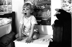 Young child kneeling on table shouting,