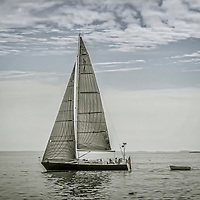 A sailboat with a dinghy tailing behind, sailing away from land in the early morning of a somewhat cloudy day.