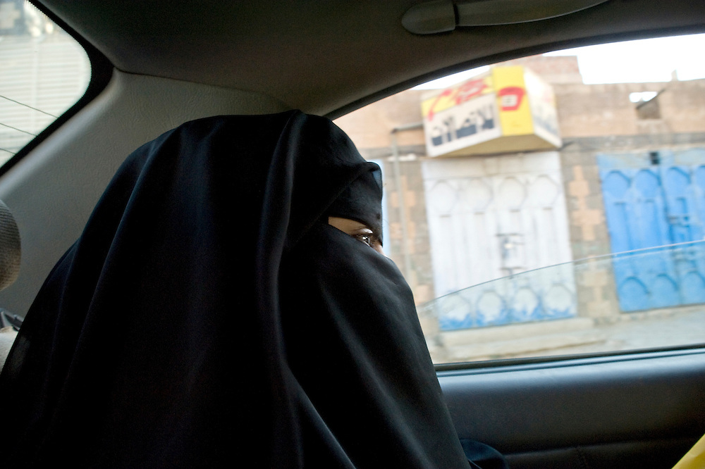 Mariam  in the taxi which is taking her  to the wedding of their cousin.