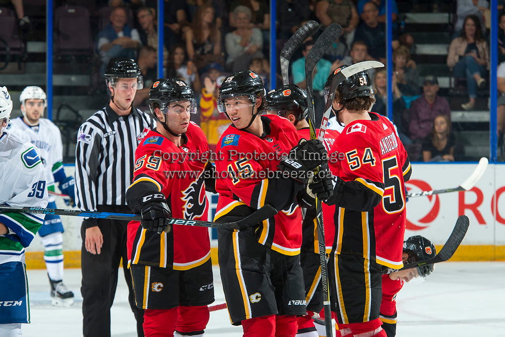 PENTICTON, CANADA - SEPTEMBER 10: Dillon Dube #59, Spencer Foo #15 and Rasmus Andersson #54 of Calgary Flames celebrate a second period goal against the Vancouver Canucks on September 10, 2017 at the South Okanagan Event Centre in Penticton, British Columbia, Canada.  (Photo by Marissa Baecker/Shoot the Breeze)  *** Local Caption ***