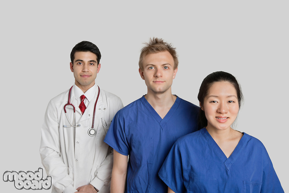 Portrait of confident multi ethnic medical team standing over gray background