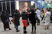 Attendees at London Fashion Show watch a live feed of the Ashish Gupta show on the second day of events throughout the capital. London Fashion Week is one of the highest profile fashion events in the world. There are 50 or so catwalk shows on the official schedule and 45+ show off schedule.