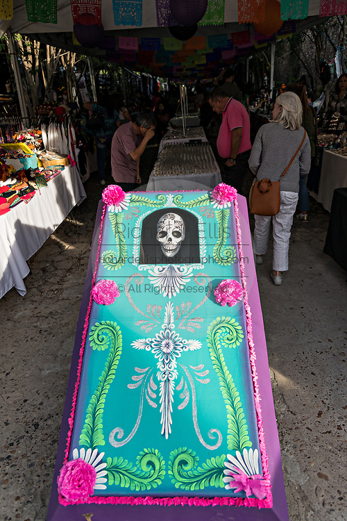 A giant decorated coffin with a skeleton at the entrance to a holiday art market during Halloween and Dead of the Dead festivals in San Miguel de Allende, Mexico.