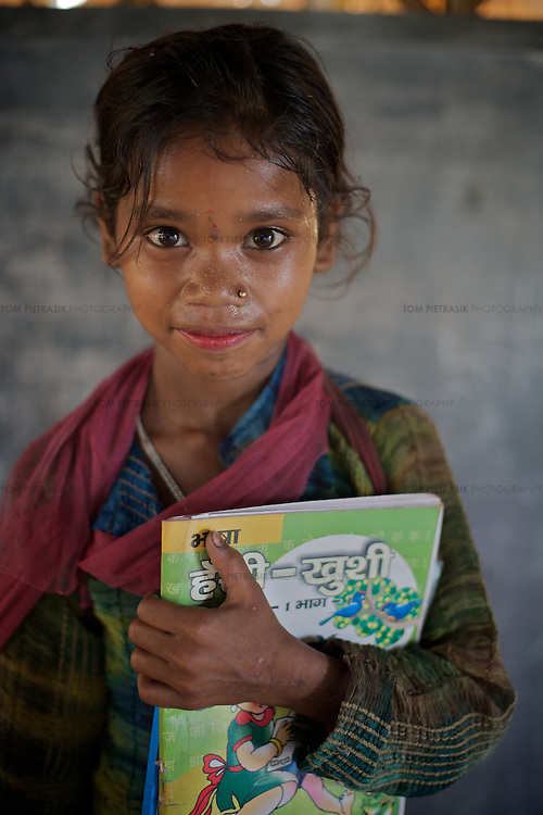 Pupil Anna, age 8, with a Hindi work book (supplied by Oxfam) at Apna Kendra bridge school for working children. Funding for the building, books, work materials and teacher's wage are all provided by Oxfam.<br />
