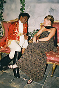 Costumed couple sitting on armchairs talking, Posh at Addington Palace, UK, August, 2004