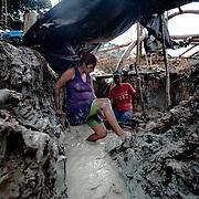 Brasile, Amazzonia, garimpo de Juma. Le miniere a cielo aperto del garimpo de Juma, dove la vita dei minatori scorre tra pericolo per un lavoro al limite e deforestazione incontrollata. Aspettando di trovare l'oro che cambi la loro vita. In questa foto una donna in cinta lavora in una delle fasi dell'estrazione dell'oro, riparandosi con un telo dalla calura estiva. Brazil, Amazonia, garimpo de Juma. The open pit mines of garimpo de Juma, where the miners work flows between danger and uncontrolled deforestation. Waiting to find the gold that changes their lives. In this picture a pregnant woman working in one of the phases of gold mining, sheltering from the summer heat with a towel.