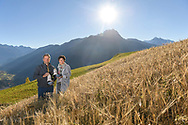 Roland and Monica Farrer in a field of barley (Hordeum vulgare), Parc Ela, Grisons, Switzerland