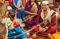 The groom smiling during a portrion of his Hindu / Indian wedding where the bride and groom are bound together and wrapped with string which is passed around them by family members.