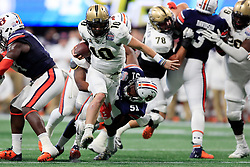 UCF Knights quarterback McKenzie Milton (10) breaks through a tackle by Auburn Tigers linebacker Richard McBryde (51) during the 2018 Chick-fil-A Peach Bowl NCAA football game on Monday, January 1, 2018 in Atlanta. (Paul Abell / Abell Images for the Chick-fil-A Peach Bowl)