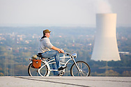 Europe, Germany, Northn Rhine-Westphalia, Ruhr area, Herten, cyclist on the heap Hoheward, in the background the cooling tower of the Evonik Steag heat and power plant Herne.....Europa, Deutschland, Nordrhein-Westfalen, Ruhrgebiet, Herten, Fahrradfahrer auf der Halde Hoheward, im Hintergrund der Kuehlturm des Evonik Steag Heizkraftwerks Herne.