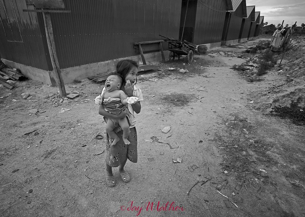 Fifty families affected by HIV and AIDS were evicted from the Borei Keila neighborhood in central Phnom Penh, Cambodia and recloated 20 kilometers (12.5 miles) to a site known as Tuol Sambo.   It is now called Cambodia&rsquo;s &ldquo;AIDS colony.&rdquo;<br /> <br /> The colony is nothing more than a series of green corrugated metal buildings with rooms no larger than 8&rsquo; x 10.&rsquo;  Stifling heat and little security are only two of the problems.  The colony has no electricity, sewage disposal or running water.  One well serves the entire community.<br /> <br /> The plight of the residents of the camp has come to the attention of over 100 international human rights and health organizations that are deeply concerned over the situation.  A letter written to government officials cites the conditions at the camp as a serious health threat, particularly to people with compromised immune systems.<br /> <br /> The residents of the colony who worked in Phnom Penh as day laborers, motorcycle taxi drivers, seamstresses and cleaners have little hope of finding work so far from the city. <br /> <br /> Pictured:  A young girl carries her crying brother while her mother prepares an evening meal at the AIDS colony.