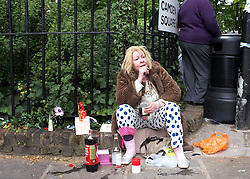 © licensed to London News Pictures. LONDON, UK.  26/07/11. A woman sits opposite the house. On the day of her funeral fans look at flowers outside the Camden house of Amy Winehouse in North London today (26 July 2011). The singer passed away on Saturday 23th July. Mandatory Credit Stephen Simpson/LNP