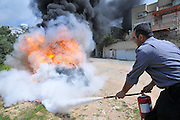 Fireman extinguishes a tire fire as part of a fire fighting drill