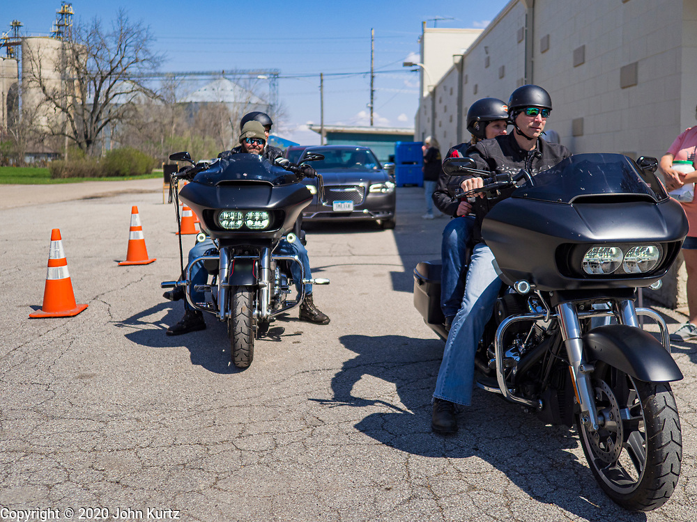 """26 APRIL 2020 - JEWELL, IOWA: Motorcyclists wait to buy """"grab and go"""" roast pork dinners in Jewell during a fund raiser Sunday. Jewell, a small community in central Iowa, became a food desert when the only grocery store in town closed in 2019. It served four communities within a 20 mile radius of Jewell. Some of the town's residents are trying to reopen the store, they are selling shares to form a co-op, and they hold regular fund raisers. Sunday, they served 550 """"grab and go"""" pork roast dinners. They charged a free will donation for the dinners. Despite the state wide restriction on large gatherings because of the COVID-19 pandemic, the event drew hundreds of people, who stayed in their cars while volunteers wearing masks collected money and brought food out to them. Organizers say they've raised about $180,000 of their $225,000 goal and they hope to open the new grocery store before summer.          PHOTO BY JACK KURTZ"""