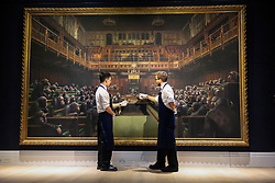 "© Licensed to London News Pictures. 27/09/2019. London, UK. Technicians view 'Banksy's artwork titled ""Dystopian View of The House of Commons Comes to London"" Est -£1.5 – £2 million during the preview of Sotheby's Frieze Week Contemporary Art Sale. The auction will take place on 3rd October 2019.  Photo credit: Dinendra Haria/LNP"