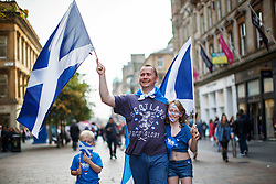 © Licensed to London News Pictures. 18/09/2014. Glasgow, UK. A family walking in Glasgow city centre with Scottish Saltire flags whilst people of Scotland going to polling stations to vote on the Scottish independence referendum on Thursday, 18 September 2014. Photo credit : Tolga Akmen/LNP