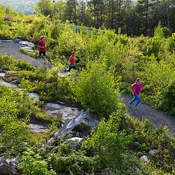 A woman and her teenage son and daughter trail running on the summit of Mount Agamenticus in York, Maine.