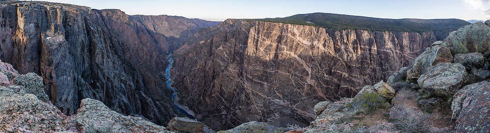 Dragon Point, Black Canyon of the Gunnison National Park, near Montrose, Colorado, USA. Pressurized molten rock was forced into 1.7-billion-year-old metamorphic rock, forming pink pegmatite stripes on Colorado's highest cliffs. With two million years to work, the Gunnison River and weathering have sculpted a vertical wilderness of rock, water, and sky. This panorama was stitched from 11 overlapping photos.