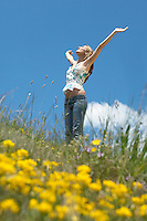 Young woman standing in field with open arms low angle view side view