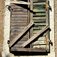 Old Wooden Shutter in Kotor, Montenegro<br /> In 1992, Serbia and Montenegro became a republic after the collapse of Yugoslavia. Then, in 2006, Montenegro became Europe's youngest country when they separated from Serbia by declaring their independence. As a result of their relative youth, their economy has not reached the levels of most developed countries. For example, their GDP per capita is less than $5,000 USD. This ranks them at 38% of the world's average. This low prosperity is reflected in their infrastructure and housing. But it also adds to the country's picturesque and unspoiled charm.