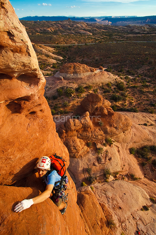 "Mario Wilde scaling the classic tower ""The Owl"" in Arches National Park"