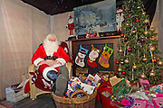 A comical feature showing the diverse and wide variety of Santa Clause's one can find in and around London. Father Christmas seems to have a wide range of appearances and different types of grottos from the elaborate Hamley's Toy Store to a garden shed in a Chobham garden centre. <br /> Pictured - Santa Clause and his grotto at Squires Garden Centre, Woking.<br /> Credit: Rick Findler / Story Picture Agency