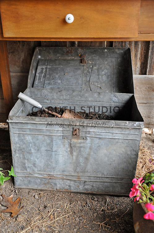 Potting bench in shed made from vintage components, potting soil in galvanized metal trunk