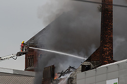 © Licensed to London News Pictures . 15/08/2018. Manchester , UK . A mill is on fire on Southall Street , believed to be at number 28 , opposite HMP Manchester ( Strangeways Prison ) . Firefighters report the fire started just before 5am this morning (15th August 2018) . Large parts of the mill , which appears to be for sale , have collapsed . Photo credit : Joel Goodman/LNP